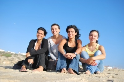 group of girl friends sitting on the beach