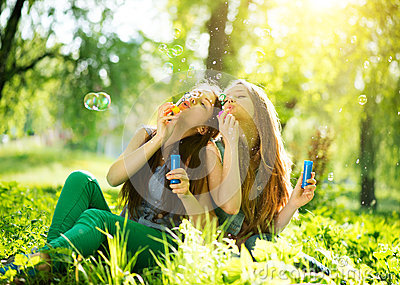 Teenage girls blowing bubbles